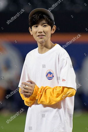 Chinese musician and actor Roy Wang prepares to throw out the first pitch before a baseball game between the New York Mets and the Miami Marlins, in New York