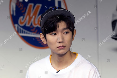 Chinese musician and actor Roy Wang sits in the dugout before a baseball game between the New York Mets and the Miami Marlins, in New York