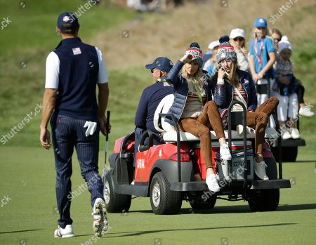 Paulina Gretzky, center left, gestures to her partner, Dustin Johnson of the US, left, as she and Jena Sims are driven in a buggy down a fairway during a foursome match on the second day of the 42nd Ryder Cup at Le Golf National in Saint-Quentin-en-Yvelines, outside Paris, France