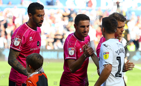Angel Rangel of QPR shakes hands with former team mate Tom Carroll of Swansea City before kick off