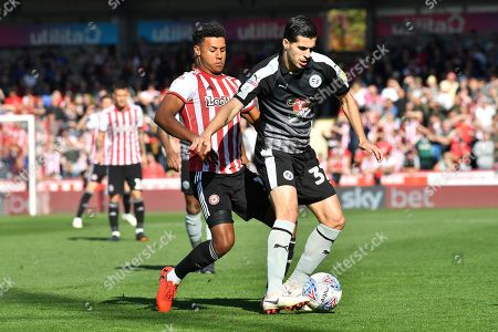 Stock Picture of Reading's Saeid Ezatolahi holds off Brentford forward Ollie Watkins (11) during the EFL Sky Bet Championship match between Brentford and Reading at Griffin Park, London