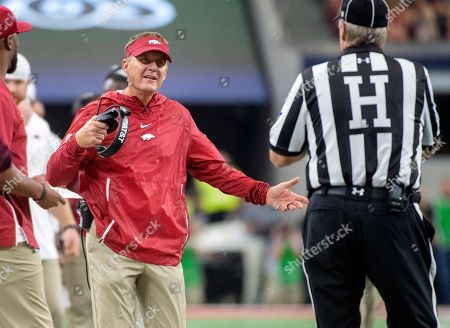 Stock Picture of Arkansas head coach Chad Morris asks head linesman Johnny Crawford for clarification on a game clock issue during the second quarter of an NCAA college football game against Texas A&M, in Arlington, Texas