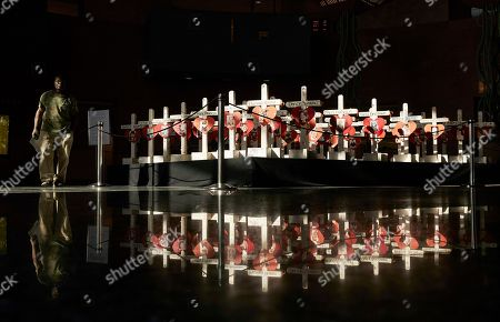 Stock Photo of A man walks by crosses on display at the Clark County Government Center in Las Vegas. The crosses had been part of a makeshift memorial along the Las Vegas Strip erected in memory of the victims of the Oct. 1, 2017 mass shooting at a country music festival in Las Vegas. A committee chaired by Nevada Gov. Brian Sandoval will work to design, fund and build a permanent memorial
