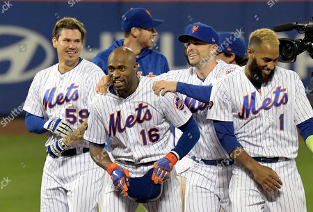 New York Mets' Jose Lobaton (59), David Wright, and Amed Rosario congratulate Austin Jackson (16) after Jackson hit a home run to defeat the Miami Marlins 1-0 during the 13th inning of a baseball game, in New York