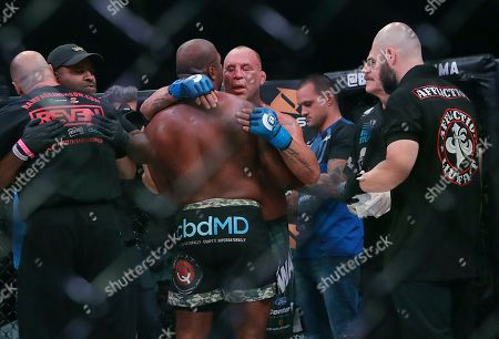 Quinton Jackson, center left, hugs Wanderlei Silva after Jackson beat Silva by technical knockout in the second round of a heavyweight mixed martial arts fight at Bellator 206 in San Jose, Calif