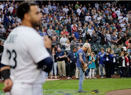Guitarist Mike McCready of the rock band Pearl Jam plays the National Anthem before a baseball game between the Texas Rangers and the Seattle Mariners, in Seattle