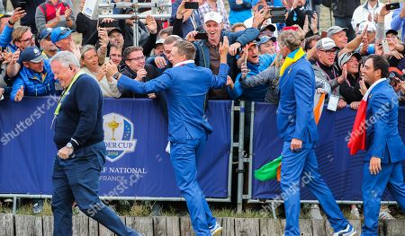 Ian Poulter of Europe celebrates with the fans with Europe Vice Captain Robert Karlsson and Francesco Molinari of Europe