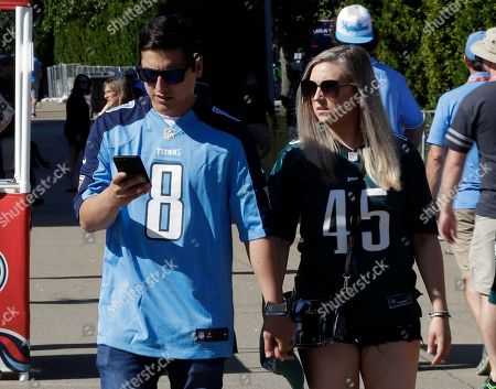 Tennessee Titans fan Nick Reed, left, and Philadelphia Eagles fan Michelle Smith, both of Virginia Beach, Va., arrive at Nissan Stadium before an NFL football game between the Tennessee Titans and the Philadelphia Eagles, in Nashville, Tenn