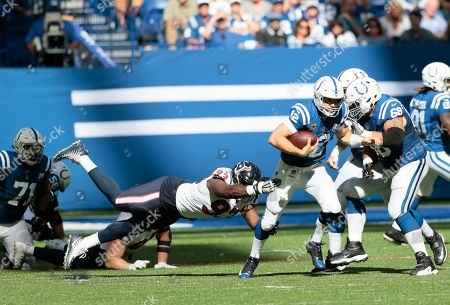 Indianapolis Colts quarterback Andrew Luck (12) runs past Houston Texans' Joel Heath (93) during the second half of an NFL football game, in Indianapolis