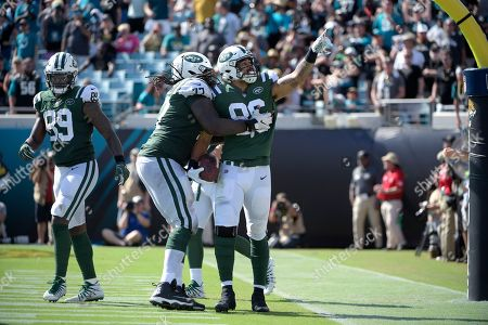 New York Jets tight end Jordan Leggett (86) celebrates with offensive guard James Carpenter (77) after catching a pass in the end zone for a 2-yard touchdown during the second half of an NFL football game against the Jacksonville Jaguars, in Jacksonville, Fla. The Jaguars won 31-12