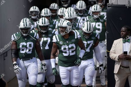 New York Jets offensive tackle Kelvin Beachum (68), offensive guard James Carpenter (77), defensive end Leonard Williams (92) and defensive end Nathan Shepherd (97), right, run onto the field with teammates before an NFL football game against the Jacksonville Jaguars, in Jacksonville, Fla
