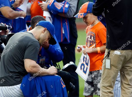 New York Mets' David Wright signs an autograph for a young fan after a baseball game against the Miami Marlins, in New York