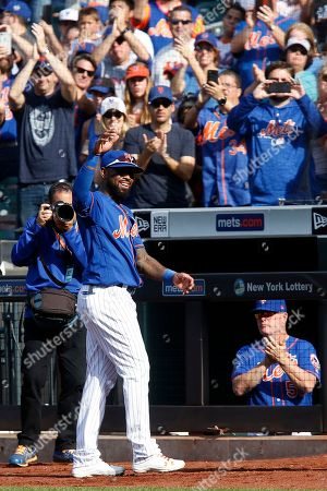 New York Mets' Jose Reyes comes out of the dugout to wave to the crowd after grounding out in the first inning of a baseball game against the Miami Marlins, in New York
