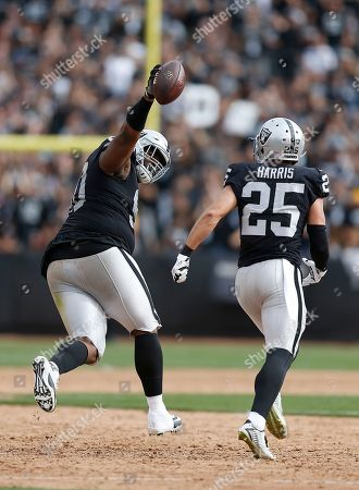 Oakland Raiders defensive tackle Johnathan Hankins, left, and defensive back Erik Harris (25) celebrate against the Cleveland Browns during an NFL football game in Oakland, Calif