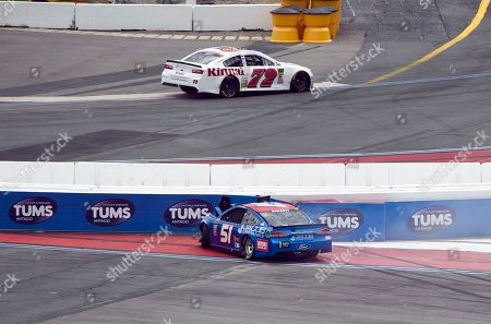 Stanton Barrett (51) hits the wall in Turn 1 as Cole Whitt (72) drives past in Turn 8 during the NASCAR Cup series auto race at Charlotte Motor Speedway in Concord, N.C