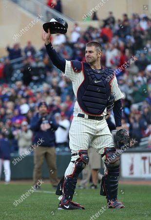Minnesota Twins' Joe Mauer, the subject of retirement talk, acknowledges a standing ovation as he donned catcher's gear and caught for one pitch against a Chicago White Sox batter in the ninth inning of a baseball game, in Minneapolis. Mauer began his career as a catcher before switching to first base. The Twins won 5-4