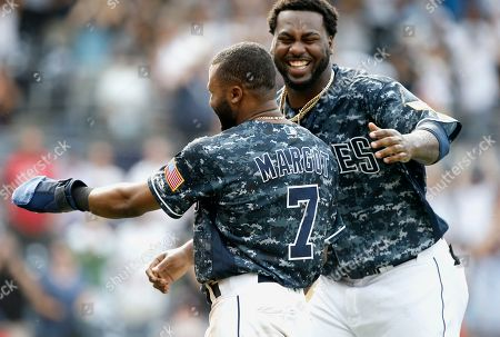Stock Picture of San Diego Padres' Franmil Reyes, right, congratulates Manuel Margot, left, after Margot slides safely into home from third base, after Arizona Diamondbacks catcher John Ryan Murphy threw to first to get Francisco Mejia, after striking out swinging during the 10th inning of a baseball game in San Diego, . The Padres won 4-3, in 10 innings