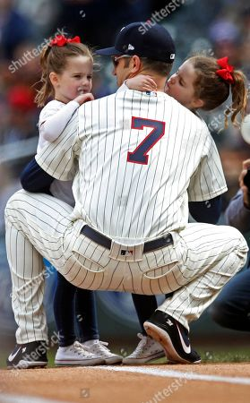 Minnesota Twins' Joe Mauer, the subject of retirement talk, is accompanied at first base by his twin daughters during a baseball game against the Chicago White Sox, in Minneapolis