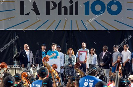 Los Angeles Phil Music & Artistic Director Gustavo Dudamel, third from left, at podium, with officials, celebrates musicians from the LA Phil, Youth Orchestra Los Angeles (YOLA), at the Celebrate LA: LA Phil 100 x CicLAvia event outside the Walt Disney Concert Hall in downtown Los Angeles . About 8 miles (13 kilometers) miles of streets stretching from downtown Los Angeles to the Hollywood Bowl are closed to motor vehicles Sunday as the city's latest celebration of the CicLAvia festival opens the lanes to bicyclists