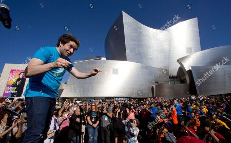 Phil Music & Artistic Director Gustavo Dudamel, conducts musicians from the LA Phil, Youth Orchestra Los Angeles (YOLA) at the Celebrate LA: LA Phil 100 x CicLAvia event outside the Walt Disney Concert Hall downtown Los Angeles . About 8 miles (13 kilometers) miles of streets stretching from downtown Los Angeles to the Hollywood Bowl are closed to motor vehicles Sunday as the city's latest celebration of the CicLAvia festival opens the lanes to bicyclists. (AP Photo/Damian Dovarganes