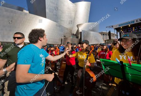 Los Angeles Phil Music & Artistic Director Gustavo Dudamel, greets young musicians from the LA Phil, Youth Orchestra Los Angeles (YOLA) at the Celebrate LA: LA Phil 100 x CicLAvia event outside the Walt Disney Concert Hall downtown Los Angeles . About 8 miles (13 kilometers) miles of streets stretching from downtown Los Angeles to the Hollywood Bowl are closed to motor vehicles Sunday as the city's latest celebration of the CicLAvia festival opens the lanes to bicyclists