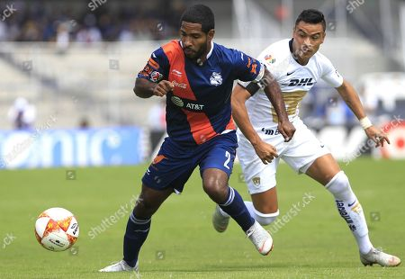 Pumas' Brayan Angulo (L) vies for the ball with Puebla's Pablo Barrera (R) during their Apertura tournament soccer match at Olympic stadium in Mexico City, Mexico, 30 September 2018.