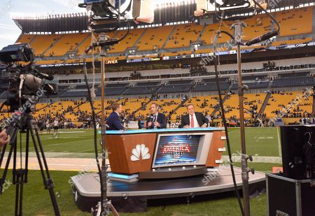 Stock Image of The NBC Sunday Night Football announcers Chris Collinsworth, center, Al Michaels, right, sit at their sideline set at Heinz Field before an NFL football game between the Pittsburgh Steelers and the Baltimore Ravens in Pittsburgh
