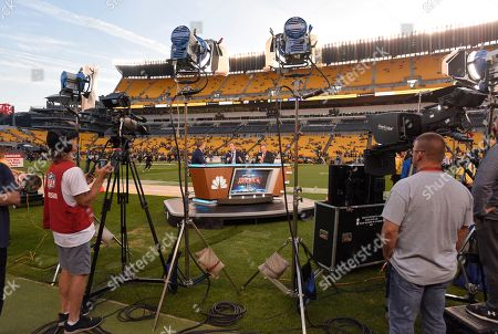Stock Picture of The NBC Sunday Night Football announcers Chris Collinsworth, center, Al Michaels, right, sit at their sideline set at Heinz Field before an NFL football game between the Pittsburgh Steelers and the Baltimore Ravens in Pittsburgh