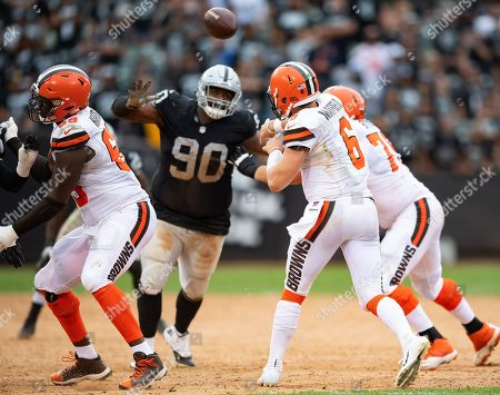 Cleveland Browns quarterback Baker Mayfield (6) gets a pas off before an impending block by Oakland Raiders defensive tackle Johnathan Hankins (90), during a NFL game between the Cleveland Browns and the Oakland Raiders at the Oakland Coliseum in Oakland, California