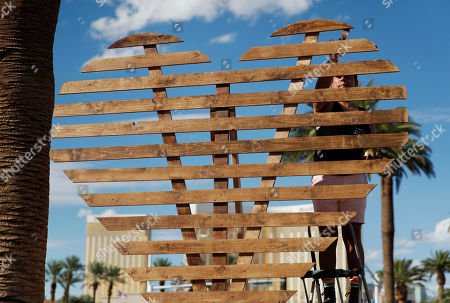 David Maldonado assembles a heart-shaped structure at a makeshift memorial for victims of the Oct. 1 2017, mass shooting in Las Vegas, in Las Vegas