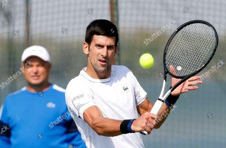 Coach Marian Vajda, left, looks Serbian tennis player Novak Djokovic returns the ball during his open practise session in Belgrade, Serbia