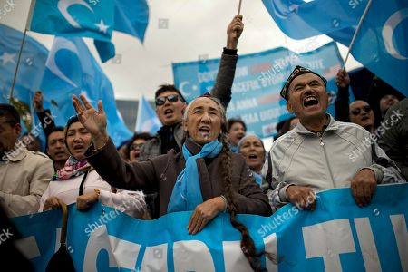 Rebiya Kadeer, center, former head of the pro-independence World Uyghur Congress, shouts slogans with others holding Uyghur flags, or pro-independence of Eastern Turkistan, during a protest in Brussels, . The protest was against internment camps, which have alarmed an United Nations panel and the U.S. government, where are estimated to be hold around one million Uyghurs and other Muslim minorities