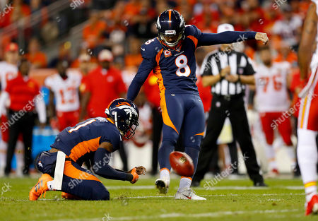 Denver Broncos kicker Brandon McManus (8) kicks a field goal as punter Marquette King (1) holds during the first half of an NFL football game against the Kansas City Chiefs, in Denver