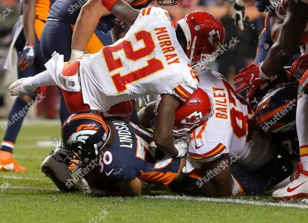 Denver Broncos running back Phillip Lindsay (30) scores a touchdown as Kansas City Chiefs cornerback Eric Murray (21) and defensive end Allen Bailey (97) defend during the second half of an NFL football game, in Denver