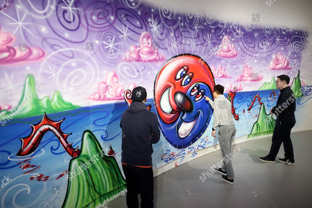 Visitors look at a work by world-renowned artist Kenny Scharf at his 'Super Pop: Universe' exhibition at a gallery in Seoul South Korea, 02 October 2018.