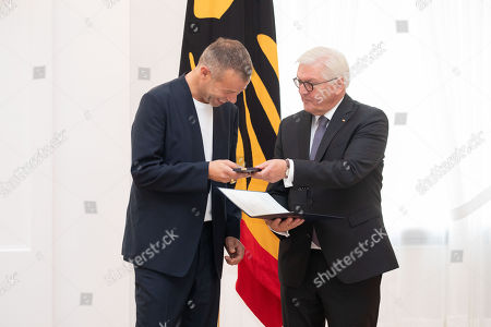 German President Frank-Walter Steinmeier (R) awards the Order of Merit to German photographer Wolfgang Tillmans (L) during a ceremony at Bellevue Palace in Berlin, Germany, 02 October 2018. The Order of Merit of the Federal Republic of Germany is awarded by the President to honour achievements of ?particular value to society?.