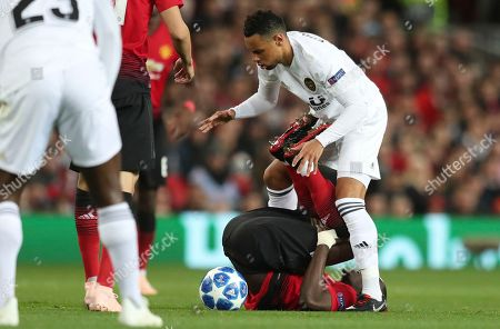 Valencia midfielder Francis Coquelin fights for the ball with ManU defender Eric Bailly, on the ground, during the Champions League group H soccer match between Manchester United and Valencia at Old Trafford Stadium in Manchester, England
