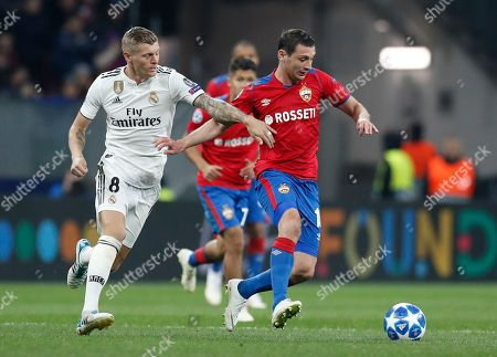 Real midfielder Toni Kroos, left, and CSKA midfielder Alan Dzagoev challenge for the ball during a Group G Champions League soccer match between CSKA Moscow and Real Madrid at the Luzhniki Stadium in Moscow, Russia
