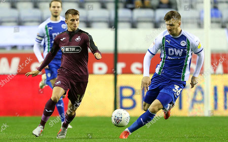 Tom Carroll of Swansea City is challenged by Lee Evans of Wigan.