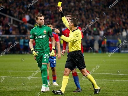 Referee Ovidiu Hategan, right, show yellow card to CSKA goalkeeper Igor Akinfeev, left, during a Group G Champions League soccer match between CSKA Moscow and Real Madrid at the Luzhniki Stadium in Moscow, Russia