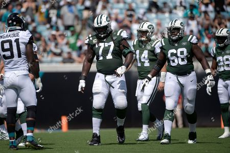 New York Jets offensive guard James Carpenter (77) and offensive tackle Kelvin Beachum (68) sets up for a play during the first half of an NFL football game against the Jacksonville Jaguars, in Jacksonville, Fla