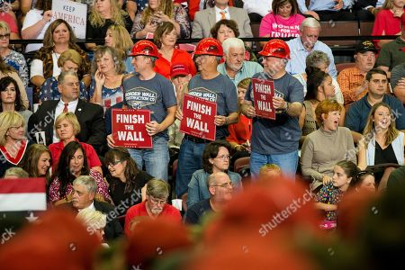 Supporters of US President Donald J. Trump wear hard hats and hold signs reading 'Finish the Wall' at a Make America Great Again rally at the Landers Center in Southaven, Mississippi, USA, 02 October 2018. President Trump has been holding MAGA rallies around the country supporting Republican candidates and speaking about what he believes are the accomplishment of his administration. During this rally, President Trump made statements mocking the testimony of Dr. Christine Blasey Ford, who has accused Supreme Court nominee Brett Kavanaugh of allegedly sexually assulting her when they were in high school.