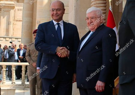 Stock Picture of Fuad Masum, Barham Salih. Former Iraq President Fuad Masum, right, shakes hands with newly elected Iraq President Barham Salih during the inauguration of the new President in Baghdad, Iraq