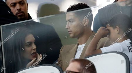 """Juventus forward Cristiano Ronaldo, center, is flanked by his girlfriend Georgina, left, and his son Cristiano Jr, as he attends a Champions League, group H soccer match between Juventus and Young Boys, at the Allianz stadium in Turin, Italy, . A lawyer for a Nevada woman alleging that soccer star Cristiano Ronaldo raped her in Las Vegas in 2009 said Tuesday her client was """"emotionally fragile"""" and agreed to an out-of-court financial settlement nine years ago because she never wanted her name made public"""