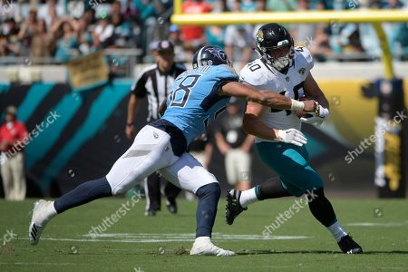Jacksonville Jaguars running back Tommy Bohanon (40) is tackled by Tennessee Titans linebacker Harold Landry (58) after catching a pass during the second half of an NFL football game, in Jacksonville, Fla. The Titans won 9-6