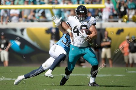 Jacksonville Jaguars running back Tommy Bohanon (40) is tackled by Tennessee Titans linebacker Harold Landry after catching a pass during the second half of an NFL football game, in Jacksonville, Fla. The Titans won 9-6
