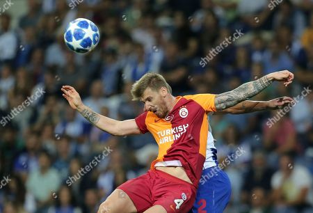 Galatasaray defender Serdar Aziz jumps for the ball with Porto defender Maxi Pereira, background, during the Champions League group D soccer match between FC Porto and Galatasaray at the Dragao stadium in Porto, Portugal