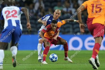 Porto defender Maxi Pereira, center left, fights for the ball with Galatasaray forward Garry Rodrigues during the Champions League group D soccer match between FC Porto and Galatasaray at the Dragao stadium in Porto, Portugal