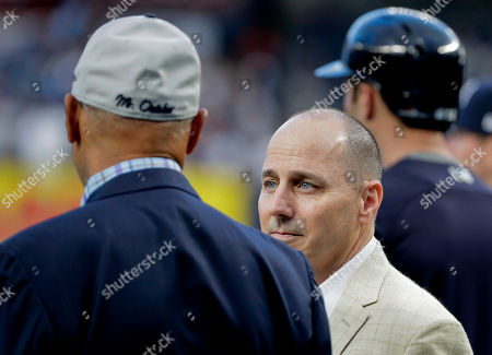 New York Yankees general manager Brian Cashman talks with former Yankees player Reggie Jackson before the American League wildcard playoff baseball game against the Oakland Athletics, in new York
