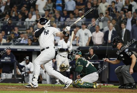 New York Yankees first baseman Luke Voit (L) follows through with a two-run RBI triple against the Oakland Athletics as Oakland Athletics catcher Jonathan Lucroy (C) and home plate umpire Jeff Wolf (R) look on during the sixth inning of the one-game elimination MLB Wildcard playoff game between the Oakland Athletics and the New York Yankees, at Yankees Stadium in New York, New York, USA, 03 October 2018.